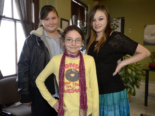Stevie Slater, 11, left, Kira Clark, 10, center, and Alyson Mickelson, 13, graduated from services at Youth Dynamics on Wednesday. (Photo: TRIBUNE PHOTO/RION SANDERS)