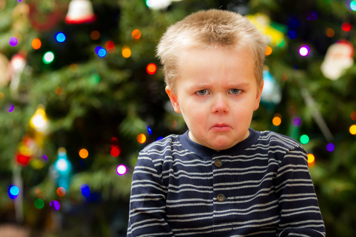 Grumpy boy in front of tree 1200x800 - The Pursuit of a Happy Holiday: Self-Care Tips for Caregivers